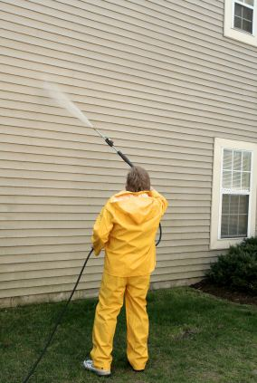 Pressure washing the siding of a house by Mendoza's Paint & Remodeling.